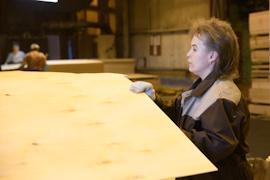 Задача сортировщицы - визуально определить дефекты готовой фанеры.