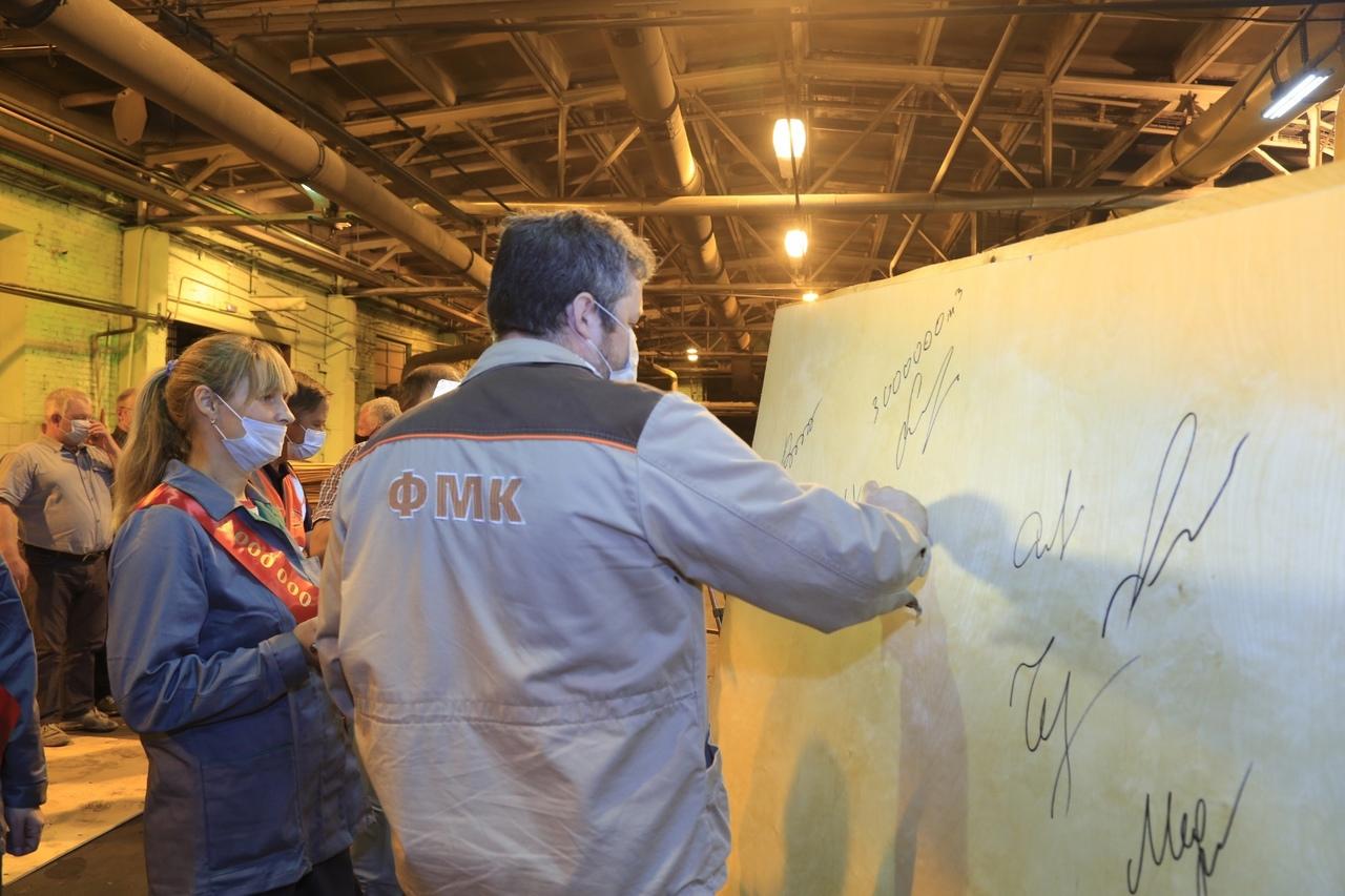 Автограф на юбилейном листа фанеры ставит начальник цеха клейки фанеры Илья Лихачев