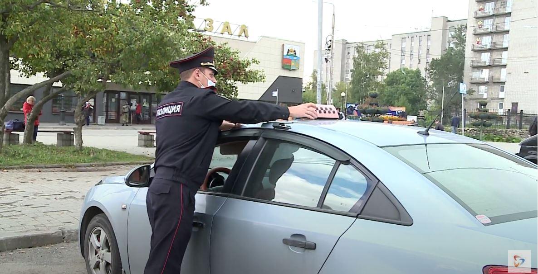 Инспекторы составляют материал и забирают опознавательный знак такси