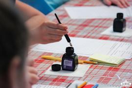 На занятии «Урок в старинной школе» дети пробуют писать пером и чернилами.